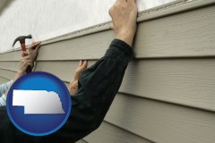 nebraska map icon and installing vinyl siding on a house